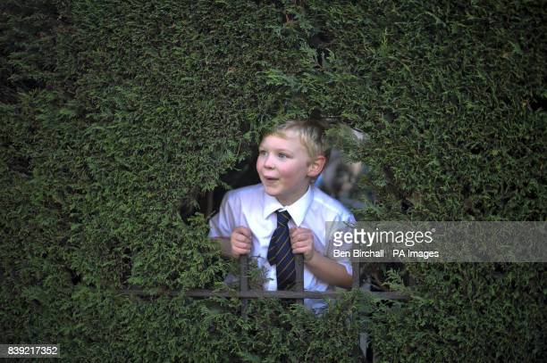A young boy from Bristol Grammar School pokes his head through the bushes and against the school playground railings to watch students from Bristol...
