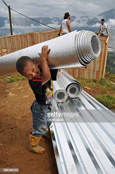 Young boy from Colombia's displaced community helping to build his new family home, an emergency pre-fabricated house built by volunteers. His family...
