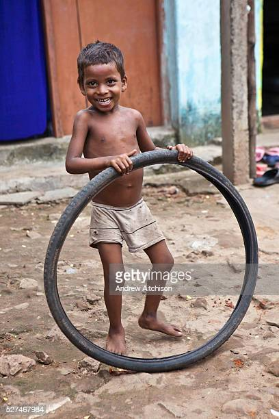 A young boy from the Pilgrim Roam slum plays with an old bicyle tyre Orissa District India