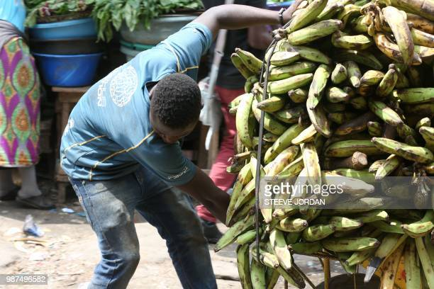 A young boy from Togo hauls a load of bananas at the Mont Bouet market in Libreville on June 25 2018 Bought in West Africa hundreds of child victims...