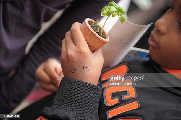 A young boy gets a potted plant during the City Harvest Presents The Brooklyn Local at Tobacco Warehouse on September 17 2011 in New York City