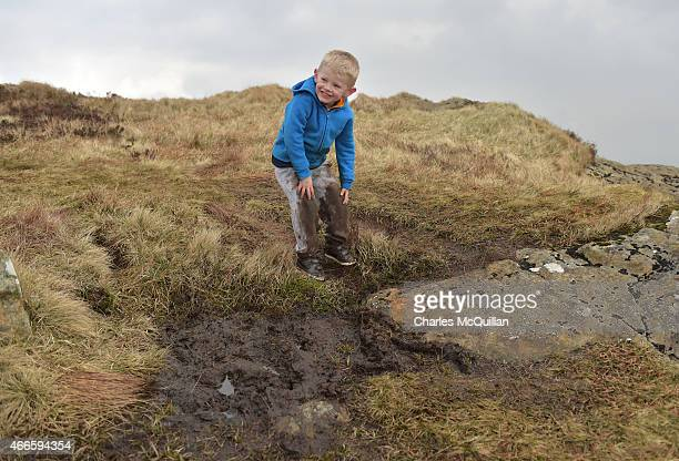 Young boy gets stuck in the mud during his climb along with hundreds of other people making the St. Patrick's Day pilgrimage to the top of Slemish on...