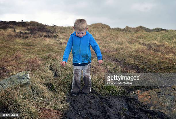 A young boy gets stuck in the mud during his climb along with hundreds of other people making the St Patrick's Day pilgrimage to the top of Slemish...
