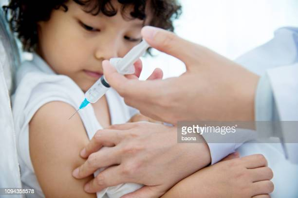 young boy getting a vaccine - vaccination stock pictures, royalty-free photos & images