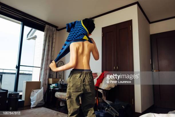 young boy getting dressed - peter lourenco bildbanksfoton och bilder