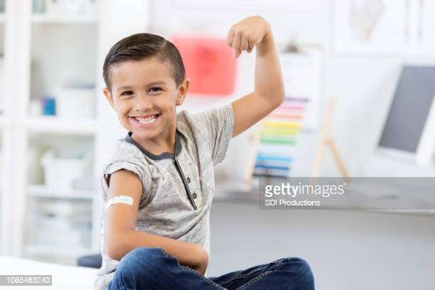 A young boy gives a toothy smile and holds up his arm to show his strength