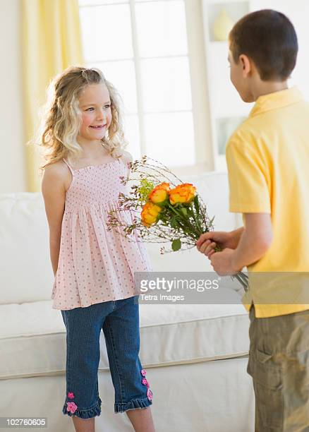 Young boy giving flowers to young girl