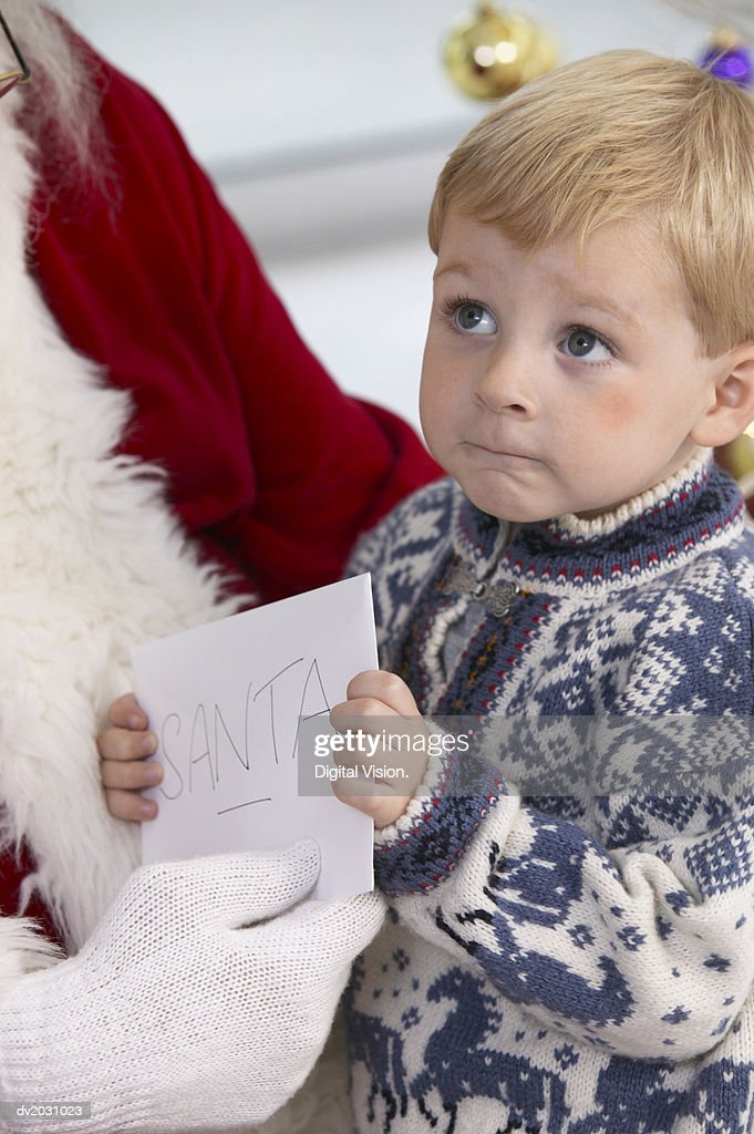 Young Boy Giving Santa Claus a Greeting Card : Stock Photo