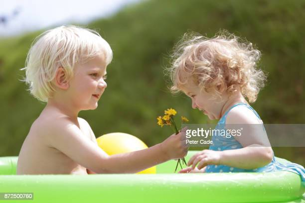 Young boy giving young girl flowers in paddling pool