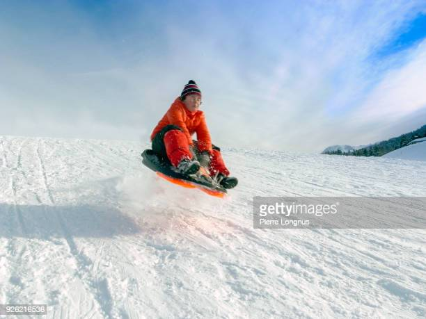Young boy going down a hill with a toboggan and getting airborne after jumping on a bump