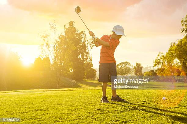 Young Boy Golfer Teeing Off During Sunset