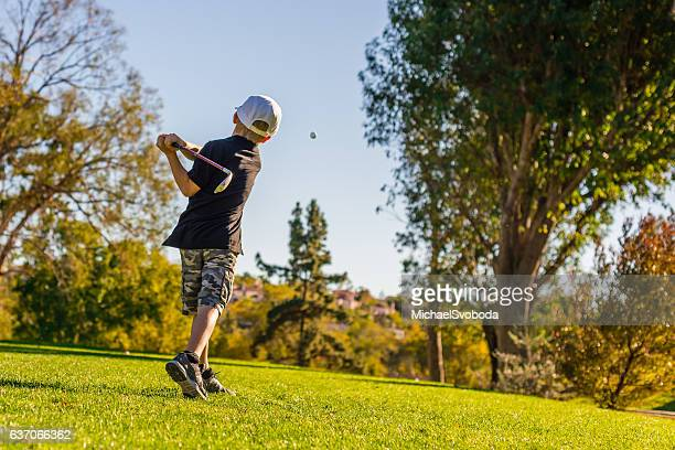 young boy golfer teeing off during sunset - junior level stock pictures, royalty-free photos & images