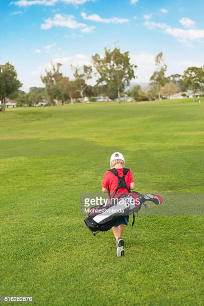 young boy golfer walking down the fairway - junior level stock pictures, royalty-free photos & images