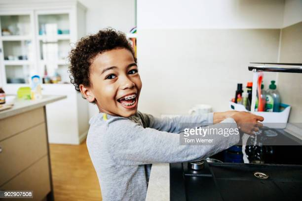 young boy grinning while washing hands in kitchen sink - handwashing stock pictures, royalty-free photos & images