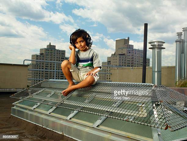 Young boy hanging out on a roof