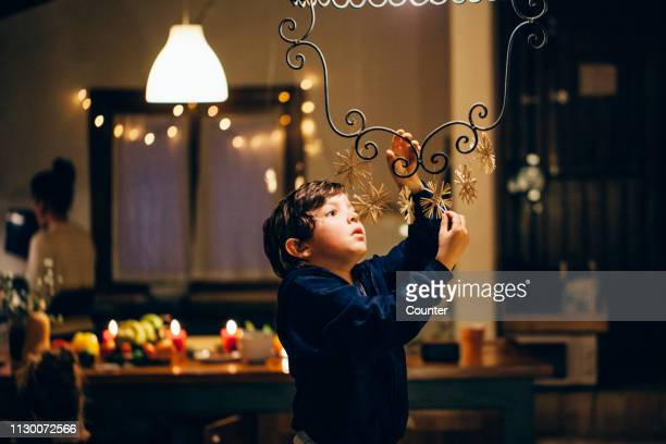 young boy hanging straw stars/christmas ornaments - decoration stock pictures, royalty-free photos & images