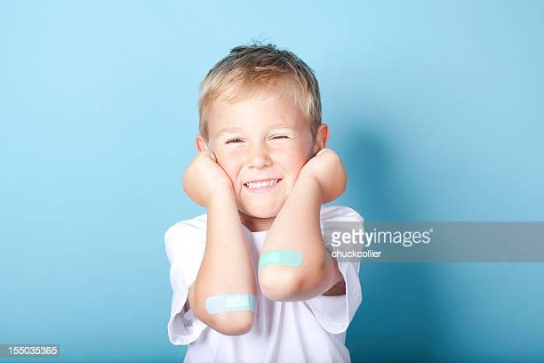 Young boy happily showing of the bandages on his elbows