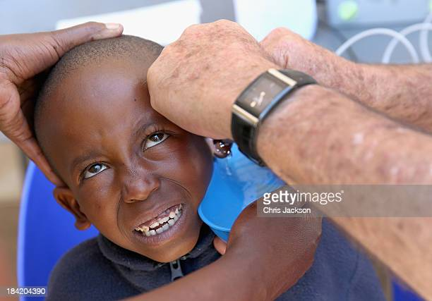 A young boy has his ears cleaned before having hearing aids fitted by the Starkey Foundation at Lesotho Cooperative College on October 10 2013 in...