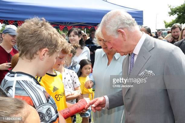 Young boy has his plaster cast signed by Prince Charles, Prince of Wales and Camilla, Duchess of Cornwall as they visit Lincoln Farmer's and Craft...