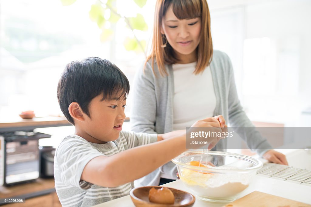 Young boy helping his mother in the kitchen : Stock Photo