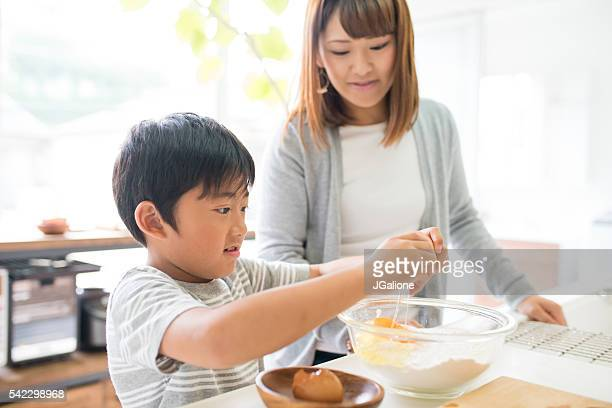 Young boy helping his mother in the kitchen