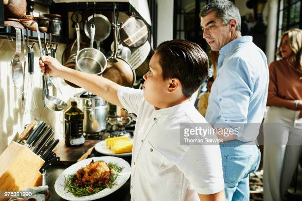 Young boy helping in the kitchen while multigenerational family prepares food for celebration meal