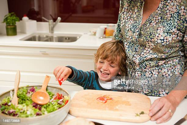 Young boy helping mother to prepare salad together at home