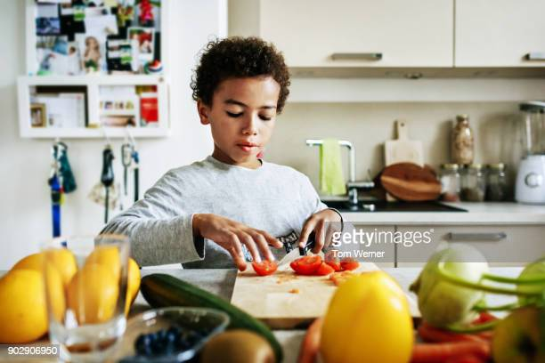 young boy helping to prepare lunch at home - north african ethnicity stock pictures, royalty-free photos & images