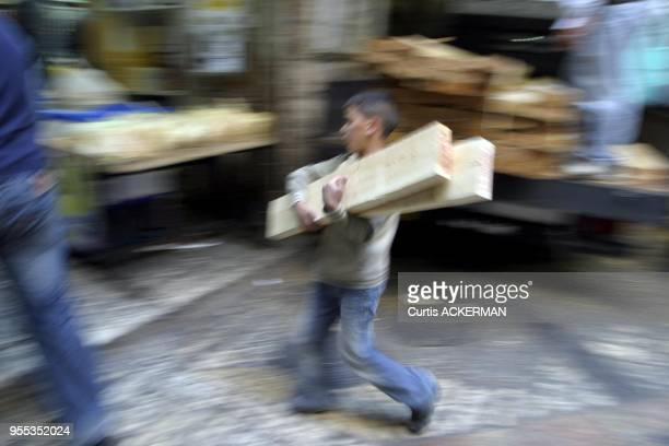 A young boy helps his father carry lumber from vendor's truck in the Muslim Quarter of Jerusalem's Old City The Muslim Quarter derives most of the...
