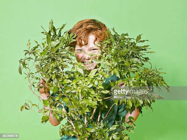 Jeune garçon cacher derrière sauterelle verte
