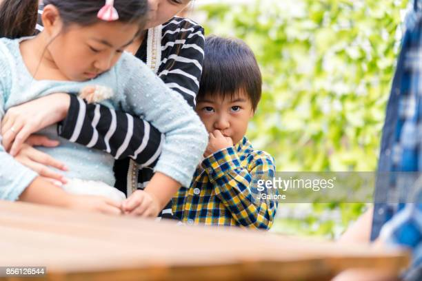 young boy hiding behind his mother looking worried - shy stock photos and pictures