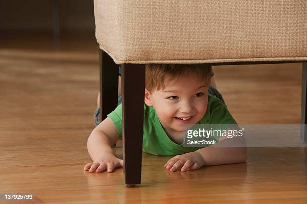 Young boy hiding underneath chair