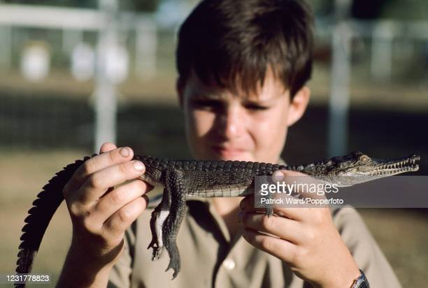 """Young boy holding a baby freshwater crocodile, or """"freshie"""", on a Queensland cattle station in Australia, circa November 1986."""