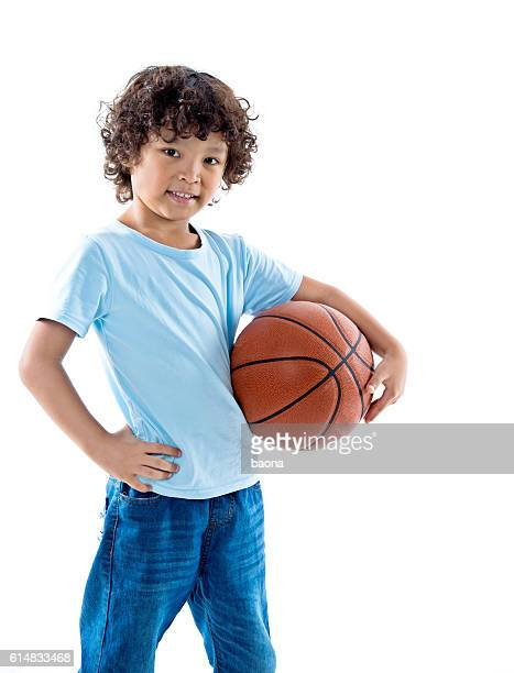 Young boy holding a basketball against white background