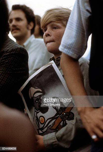 A young boy holding a Black Panther publication listens to Black Panther Party leader Fred Hampton speaking at the Band Shell in Grant Park Chicago...