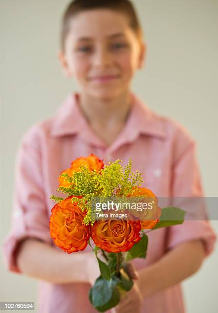 Young boy holding a bouquet of roses