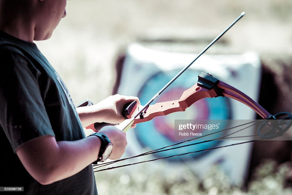 A young boy holding a bow and arrow during archery practice at camp in Colorado : Stock Photo