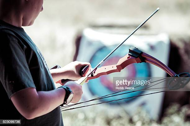 a young boy holding a bow and arrow during archery practice at camp in colorado - robb reece stock pictures, royalty-free photos & images