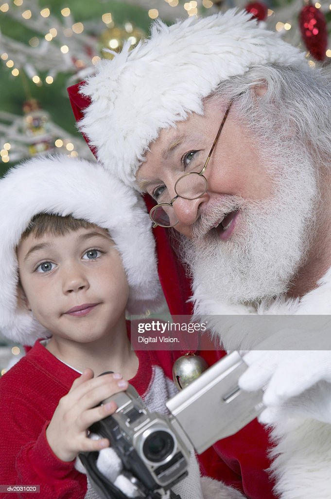 Young Boy Holding a Camcorder, Santa Claus Talking to Him : Stock Photo