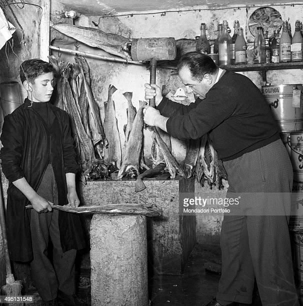 A young boy holding a cod on a stone worktop while a fishmonger gets ready to hit the fish with a hammer The procedure is part of the preparation of...