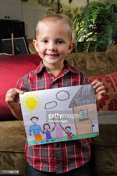 Young boy holding a family drawing at home