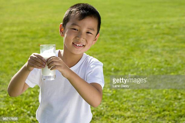 Young boy holding a glass of milk