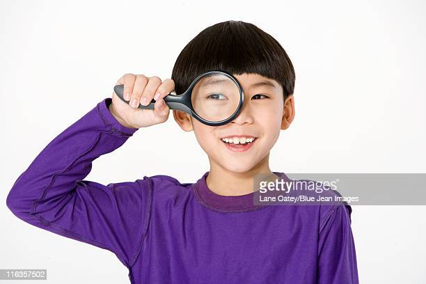 Young boy holding a magnifying glass up to his eye