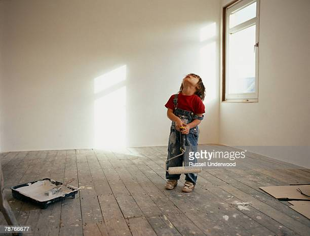 A young boy holding a paint roller and looking up