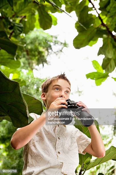 young boy holding a pair of binoculars