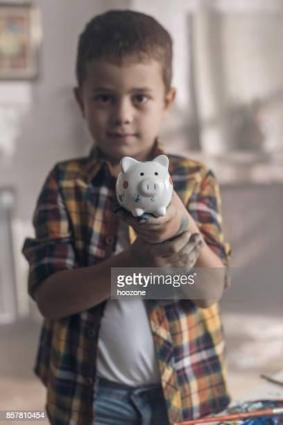 kleiner junge hält ein sparschwein in einem atelier - nur jungen stock-fotos und bilder