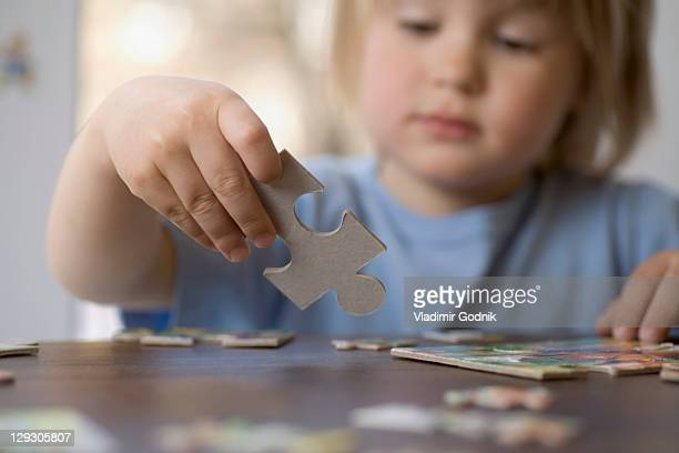 A young boy holding a puzzle piece