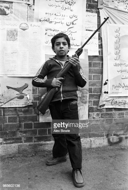 A young boy holding a rifle is seen outside the former US embassy building where Iranian students hold 52 US diplomats hostage Teheran 6th November...
