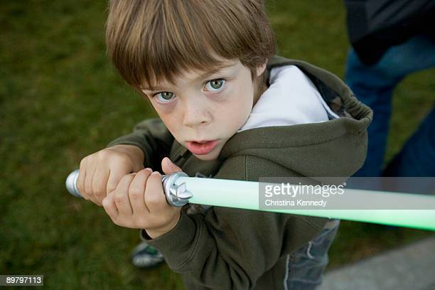 A young boy holding a toy sword