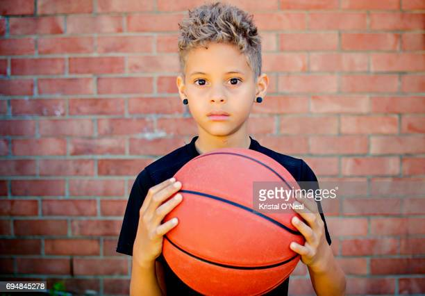 young boy holding basketball in hands with serious face - only boys stock photos and pictures